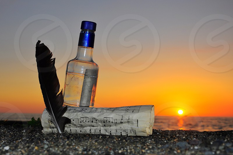 white paper near black feather and clear glass bottle photo