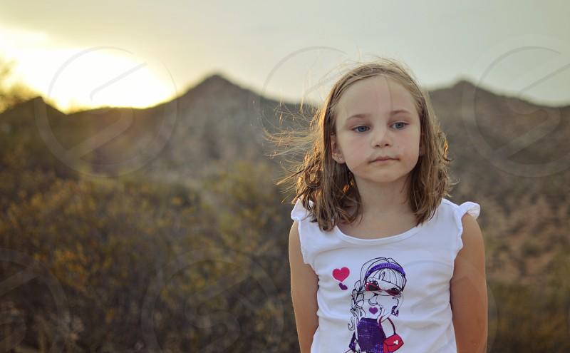 blonde girl wearing a cartoon girl print white ruffle shoulder cotton top photo