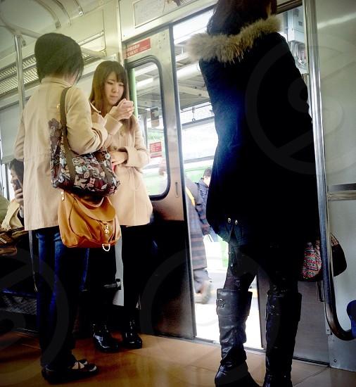 2 woman standing near the train door photo