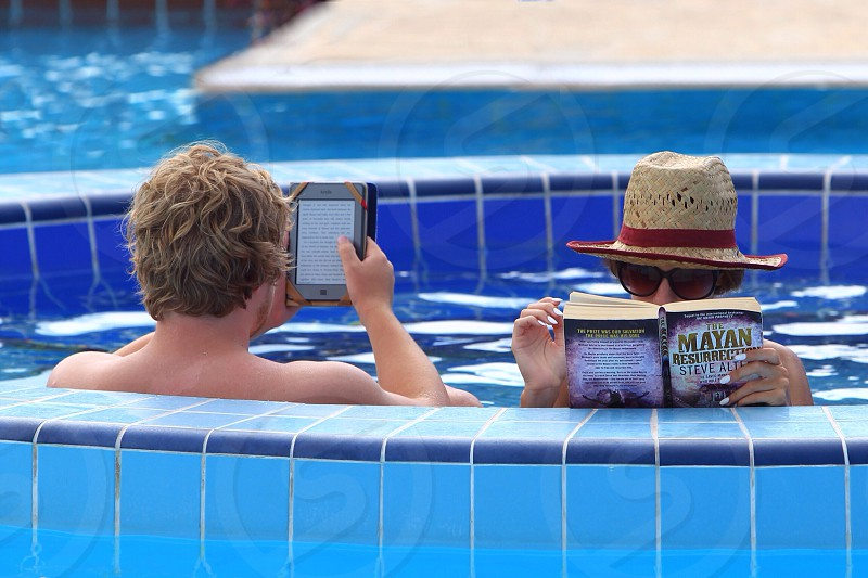Reading book ipad turquoise tropical pool cooling couple relax tranquil peace water photo