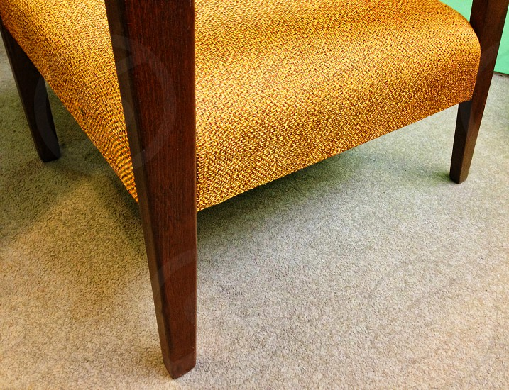 Detail of mid-century chair with gold seat and brown legs photo