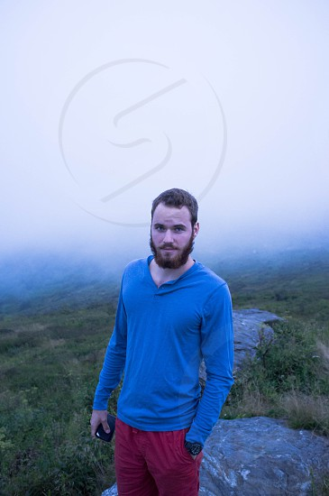 man in blue long sleeved shirt standing in a foggy field photo