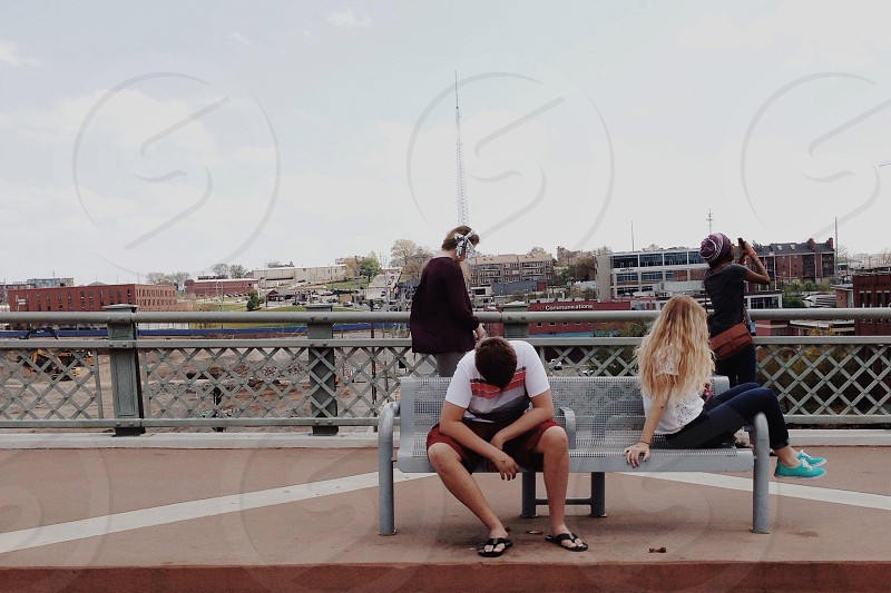 three men and one woman sitting on gray bench photo