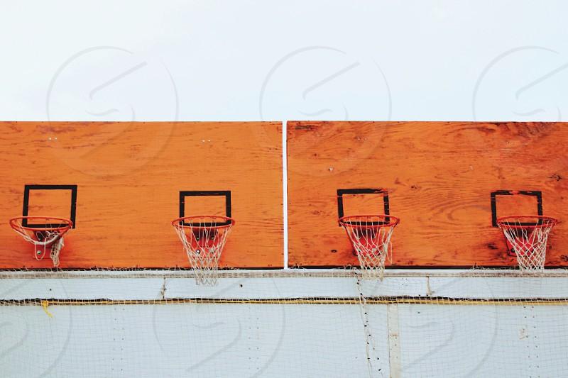 Basketball hoops with nets on weathered orange playwood backboards photo
