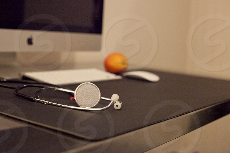 shallow focus photography of black and silver stethoscope on top of black desk with silver iMac Apple bluetooth keyboard Apple Magic Mouse and orange photo