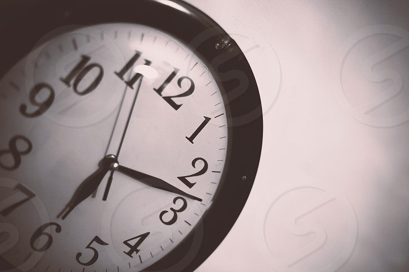 Closeup view of an old retro clock on white wall. photo