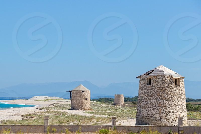 Ancient windmills on Agios Ioannis beach Lefkada Greece photo