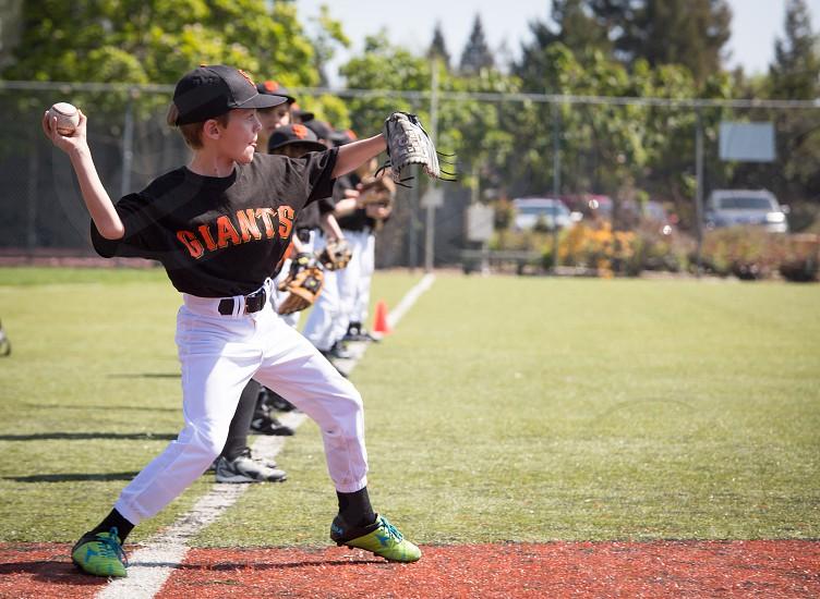 Baseball youth throwing the ball photo