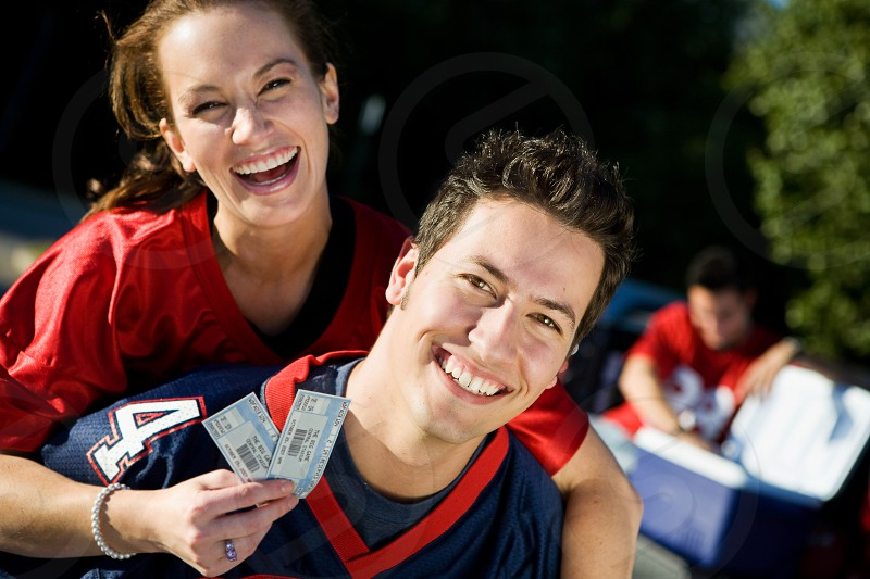 Tailgating: Laughing Couple Ready For Big Game  people; Caucasian; happy; cheerful; smiling; toothy smile; man; male; woman; female; fan; football; jersey; friends; outdoors; 20s; party; tailgate; tailgating; tailgating party; sport; celebration; fun; laughing; piggyback; carrying; holding; ticket; admission; looking at camera;  photo