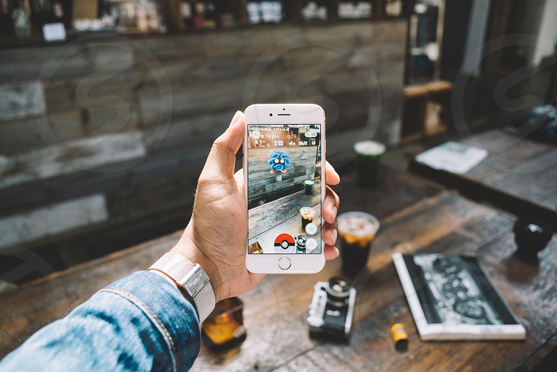 person playing pokemon go using gold iphone 6 near brown wooden table photo