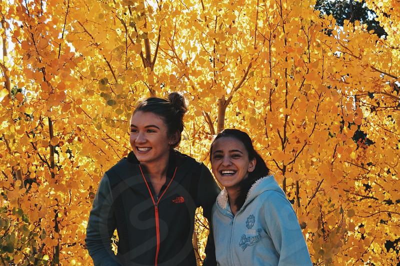 2 women in hoodies standing near brown leaf tree smiling photo