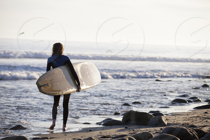 woman wearing black rash guard carrying white surfboard standing on the seashore photo