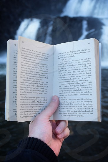person holding book at page 133 photo