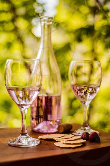 Rosé wine outdoors green trees blurred background wood table crackers strawberries cork. photo