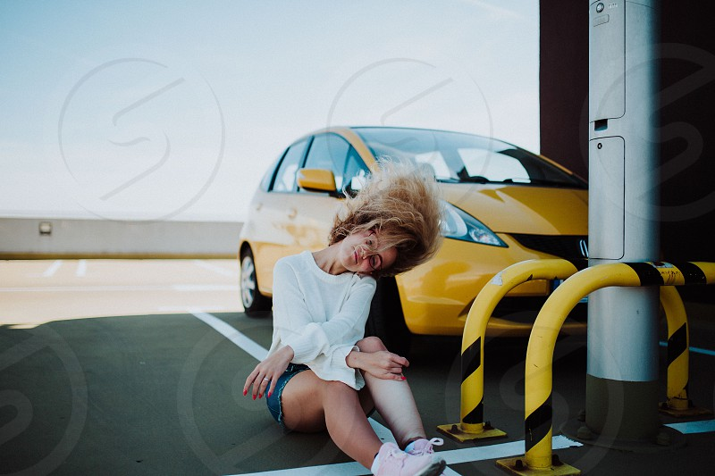Stylish girl posing at the parking near yellow car photo