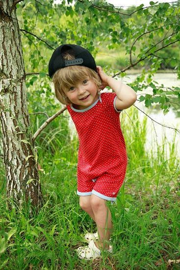 boy with blonde hair wearing black snapback cap and red and white printed romper and white clog shoes standing on green grass besides tree bark and riverside during daytime photo