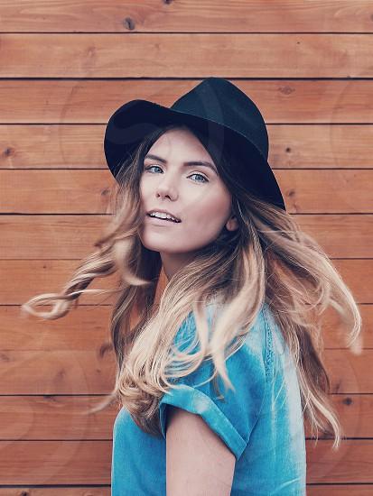 woman in blue shirt wearing black fedora hat photo