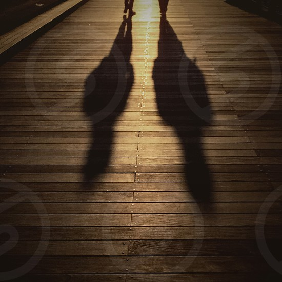 two peoples shadows on a wood deck photo