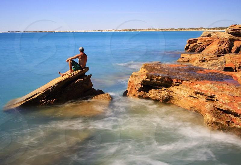 man sitting of brown rock photo