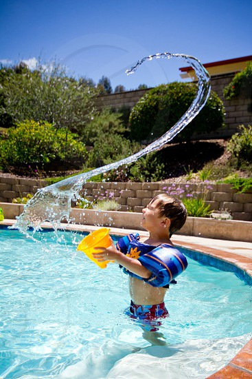 boy in shallow pool throwing water over during daytime photo