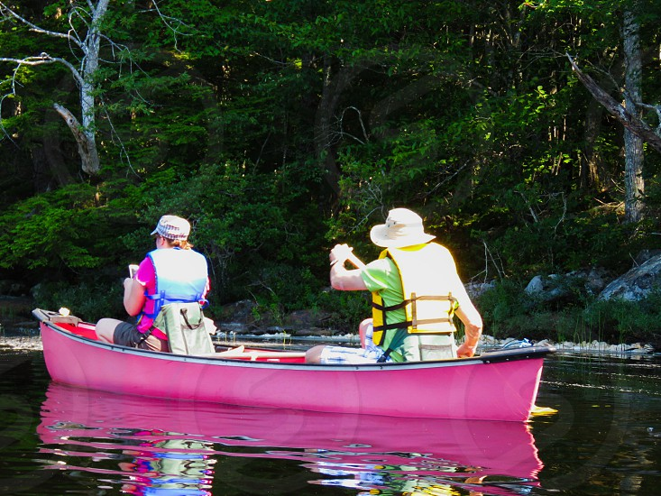 Young couple canoe paddle summer red life jackets sun hats looking at cell phone calm water lake reflections  trees adventure nature photo