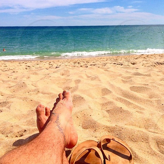 Man's feet on beach with flipflops photo