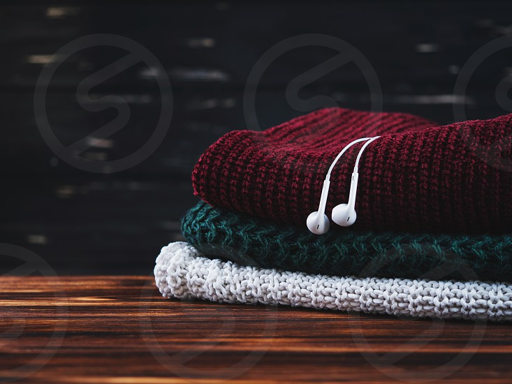 several multi-colored sweaters lie on a wooden shelf. Headphones on warm clothes. The concept of listening to music in cold weather photo