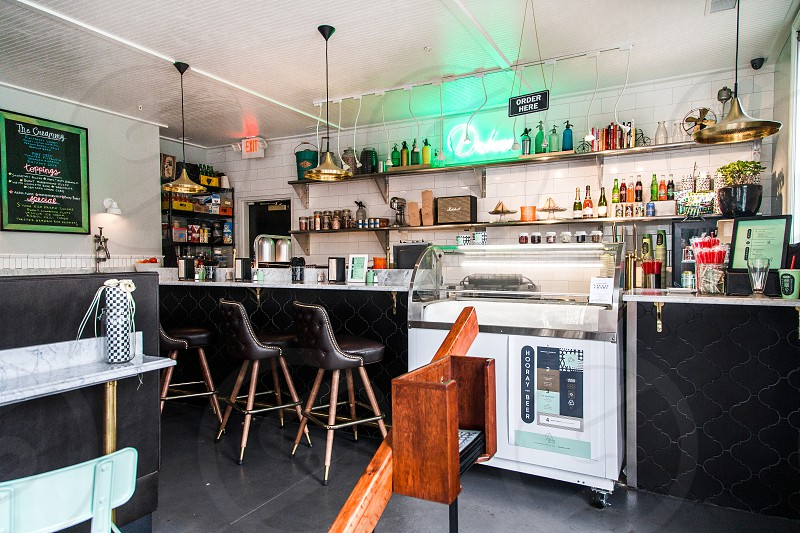 A quirky well lit space with hints of retro here and there including neon and 70s style chairs. photo