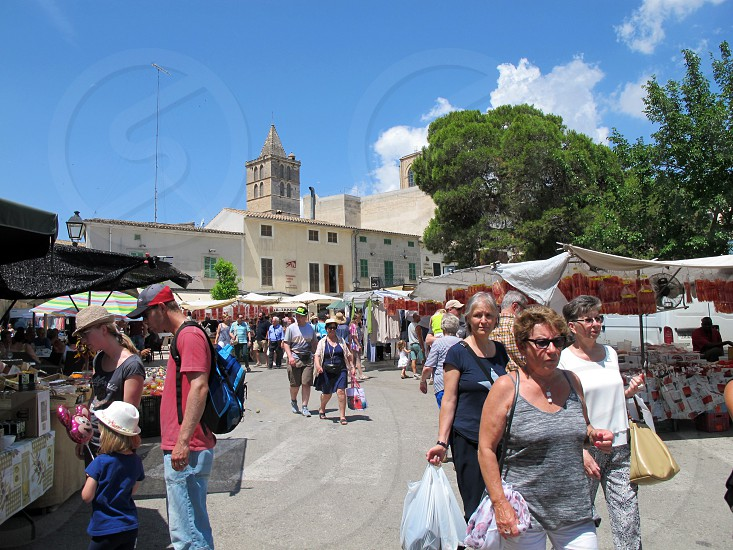 SINEU MALLORCA/ SPAIN June 10 2015: historical town Sineu (Mallorca Spain) with church Nostra Senyora dels Angels and weekly market for local products and cloth. People visiting the market photo