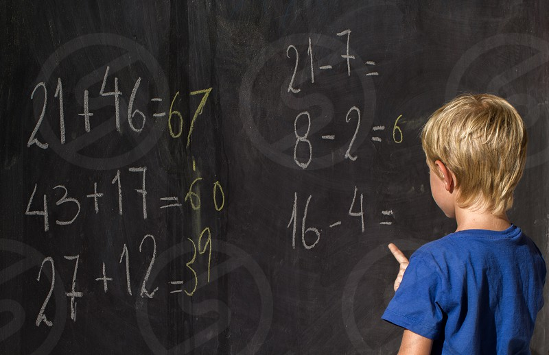 kid studying mathematic on the blackboard photo