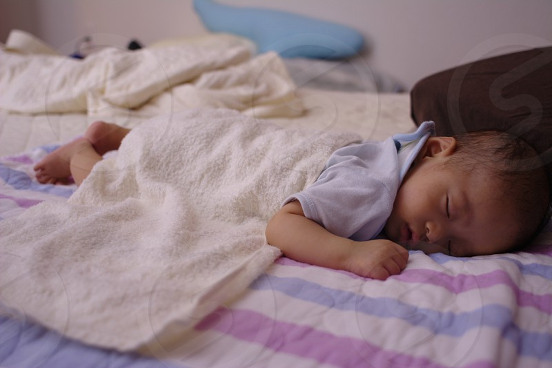 baby in blue tops covered with white towel in white blue and pink stripes bed distant from blue pillow photo