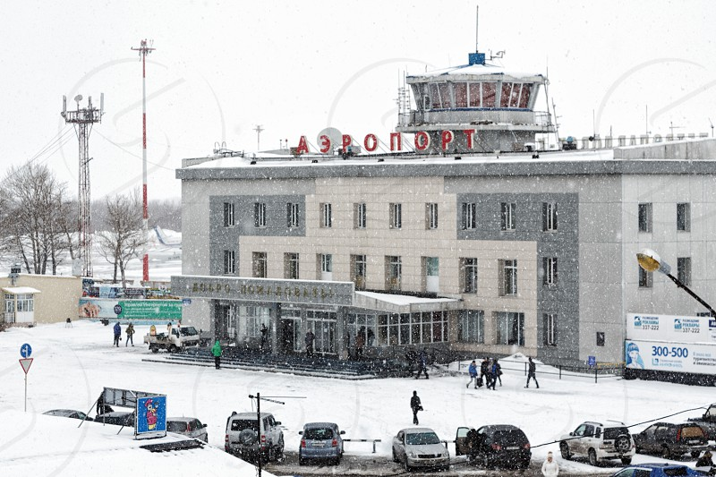 PETROPAVLOVSK KAMCHATKA PENINSULA RUSSIAN FAR EAST - MARCH 19 2015: Winter view of building of commercial airport terminal Petropavlovsk-Kamchatsky station square; during snowfall poor visibility photo