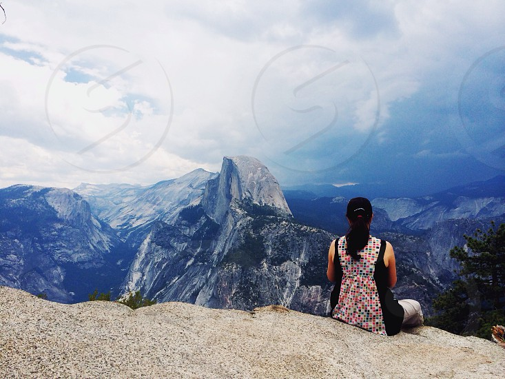 woman sitting on mountain cliff photo