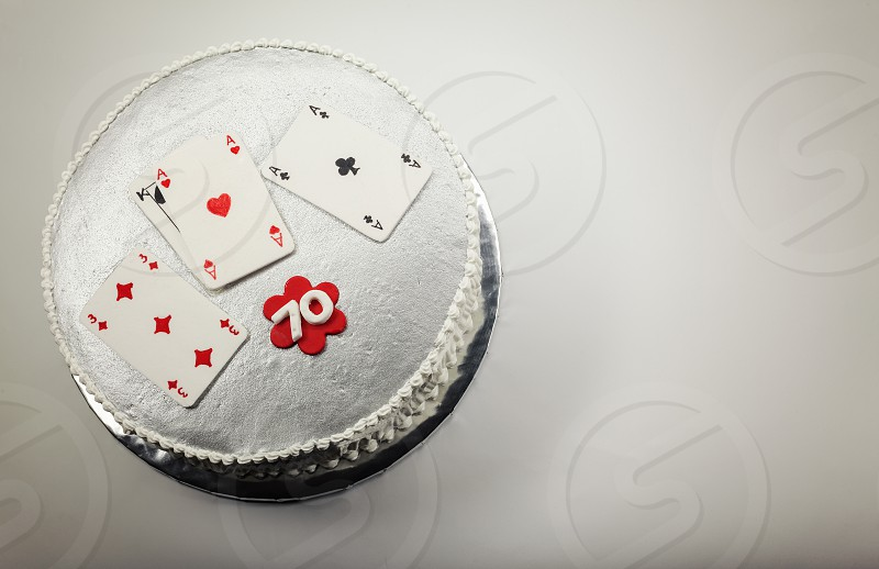 Design and decoration of a 70 birthday cake with gambling cards on top.  photo