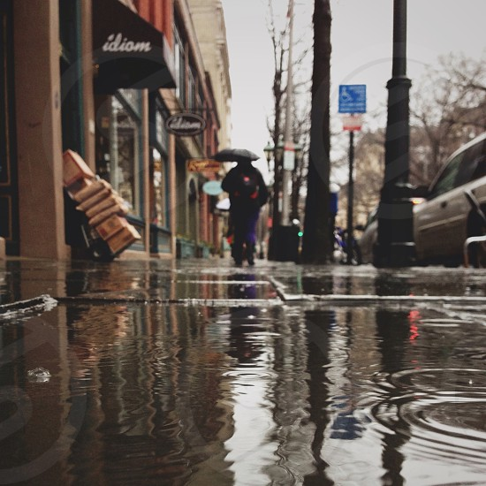 person using black umbrella in small flood filled street photo
