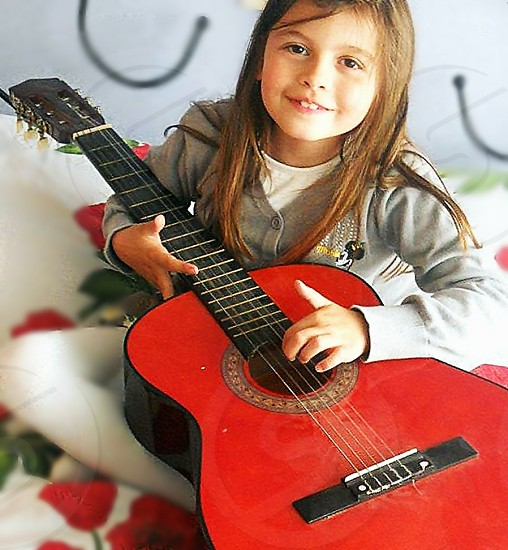 girl in grey button up cardigan holding black and red acoustic guitar smiling photo