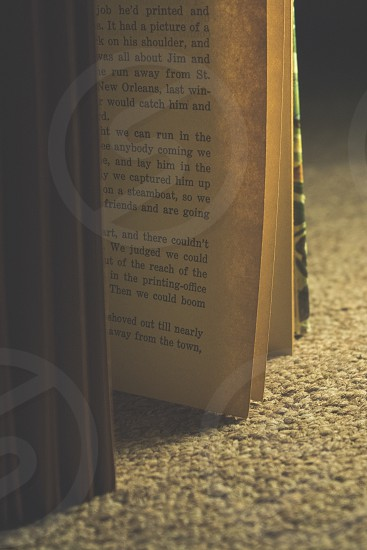 open book standing on its side on carpet photo