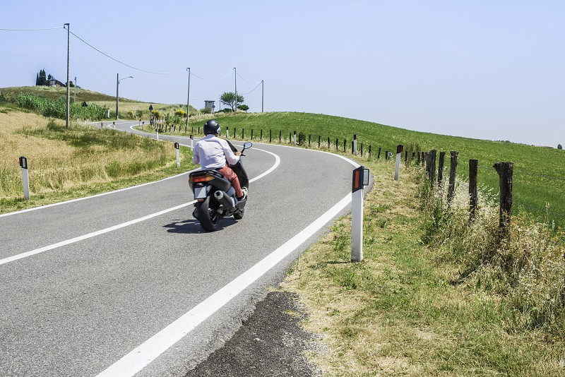 Scooter travels on a road in Italy photo