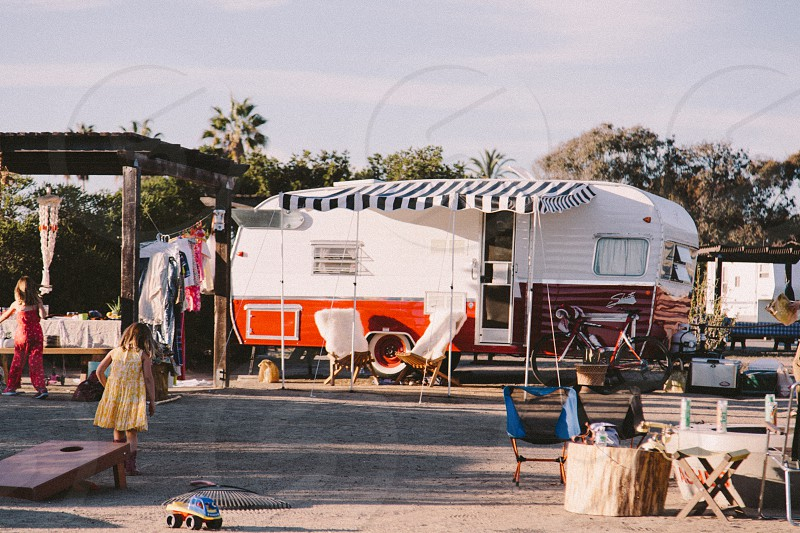 orange and white camping trailer in an area with other people photo