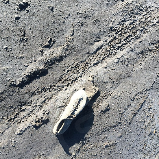 white lace up shoes left on grey sand near tire track at daytime photo