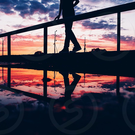 Silhouette of person standing beside handrails photo