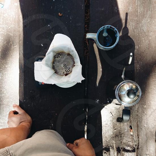 black liquid straining through white cloth by blue ceramic mug and black silver french press photo