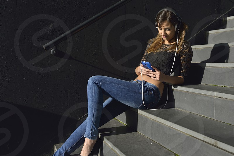 Woman play music with smartphone photo