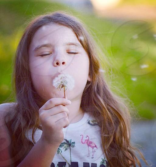Blowing girl wishing magic fun face portrait  photo