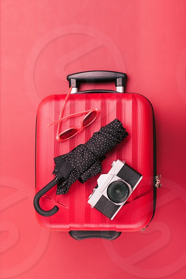 Red travel suitcase with red sunglasses old camera black umbrella on red background. Minimal style photo