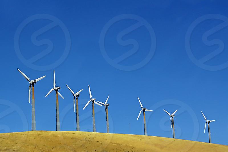 Portion of Windmill farm on a hill against a blue sky. photo