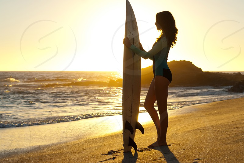 Woman young woman surfer surfboard sunset silhouette ocean Pacific Ocean waves water sunlight wetsuit sand beach standing golden  photo