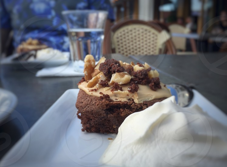 brownie with nuts and cream on top near whip cream on top of ceramic plae photo