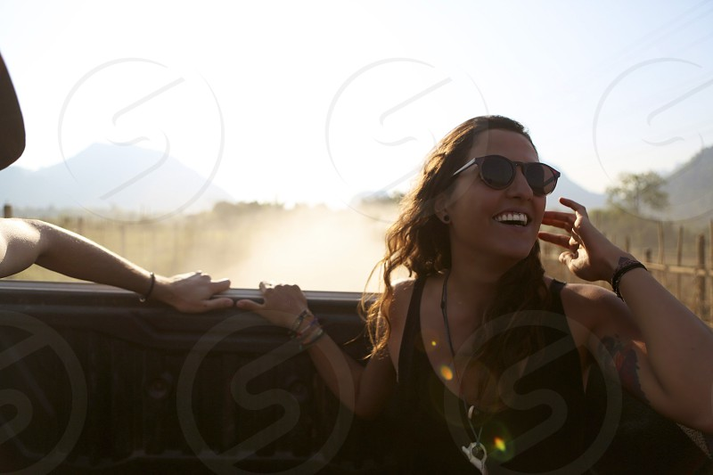 woman sitting at the back of running car wearing black sunglasses smiling with her left arm touching her hair during daytime photo