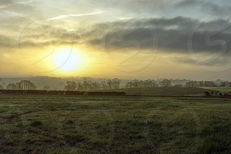 Sunrise in winter on misty morning over Staffordshire fieldsUnited Kingdom. photo